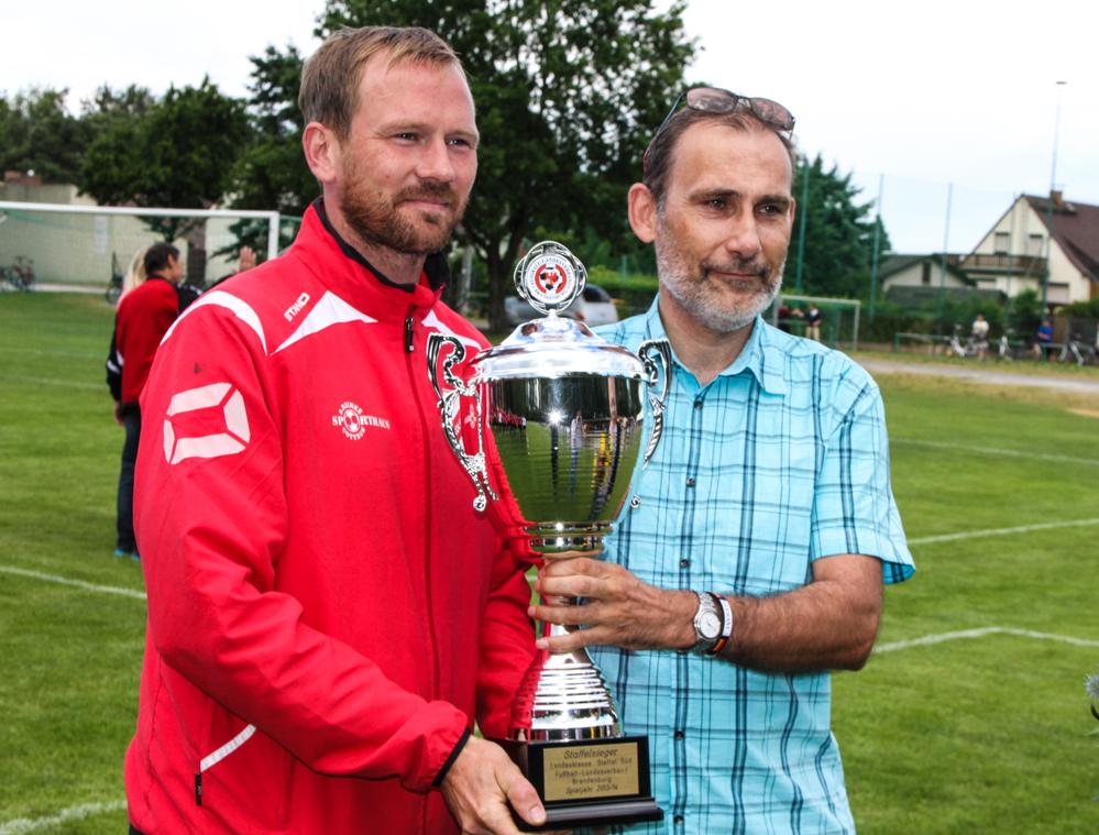 KSV-Co-Trainer David Brincker nimmt aus der Hand von FLB-Vizepräsident Fred Kreitlow den Meisterpokal entgegen.